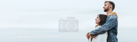 Photo for Panoramic shot of happy man hugging cheerful girlfriend - Royalty Free Image