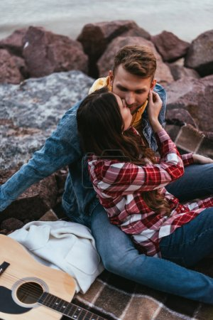 Photo for Selective focus of couple kissing near acoustic guitar - Royalty Free Image
