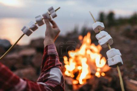 Foto de Vista recortada de pareja sosteniendo palos con malvaviscos hinchados cerca de la hoguera - Imagen libre de derechos