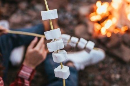 Foto de Foco selectivo de malvaviscos hinchados en palos cerca de pareja y hoguera - Imagen libre de derechos