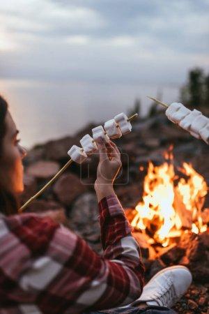 Foto de Enfoque selectivo de niña sosteniendo palo con malvaviscos hinchados cerca de la hoguera - Imagen libre de derechos