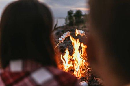 Foto de Foco selectivo de malvaviscos hinchados en palos cerca de la hoguera y la pareja - Imagen libre de derechos