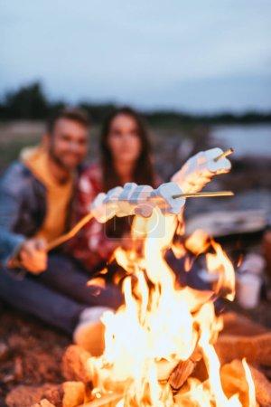 Foto de Foco selectivo de malvaviscos hinchados en palos cerca de hoguera ardiente y pareja - Imagen libre de derechos