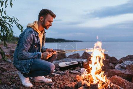 Foto de Hombre feliz tostando malvaviscos en palos cerca de la hoguera - Imagen libre de derechos