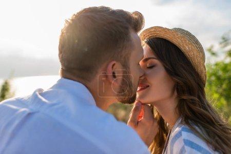 Photo pour Foyer sélectif de barbu homme baisers heureux jeune femme - image libre de droit