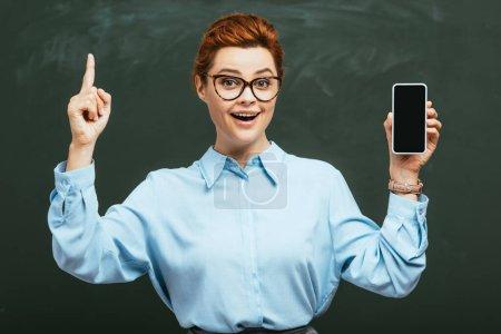 Photo pour Professeur joyeux dans les lunettes tenant smartphone avec écran blanc près du tableau noir - image libre de droit