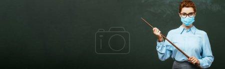 Photo pour Image horizontale de l'enseignant dans un masque médical tenant un bâton de pointage près du tableau - image libre de droit