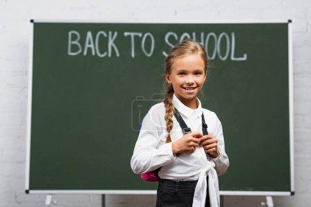Photo pour Foyer sélectif de l'adorable écolière avec sac à dos souriant à la caméra près du tableau noir avec inscription de retour à l'école - image libre de droit