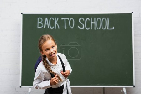 Photo for Cheerful schoolgirl with backpack smiling at camera near chalkboard with back to school inscription - Royalty Free Image