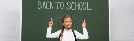 Photo for Horizontal concept of happy schoolgirl pointing with fingers at back to school inscription on chalkboard - Royalty Free Image
