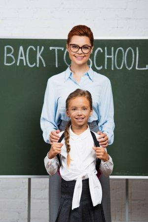 Photo pour Joyeux professeur toucher les épaules de heureuse écolière près de tableau noir avec retour à l'école lettrage - image libre de droit