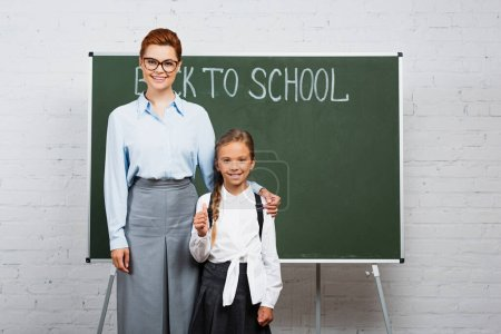 Photo for Smiling teacher touching shoulder of happy schoolgirl near chalkboard with back to school lettering - Royalty Free Image