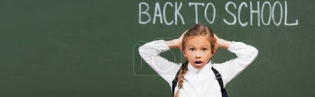 Photo for Panoramic shot of shocked schoolgirl touching head near chalkboard with back to school inscription - Royalty Free Image