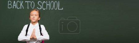 Photo pour Concept panoramique d'écolière mignonne debout avec les mains priantes près du tableau noir avec lettrage de retour à l'école - image libre de droit