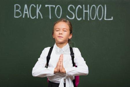 Photo pour Mignonne écolière avec les yeux fermés tenant les mains priantes près de retour à l'école lettrage sur tableau noir - image libre de droit