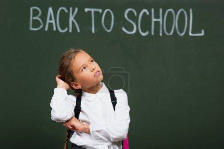 foyer sélectif d'écolière coûteuse toucher la tête tout en regardant vers le haut près de tableau noir avec inscription de retour à l'école