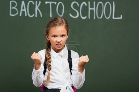 Photo for Selective focus of angry schoolgirl looking at camera and showing clenched fists near chalkboard with back to school lettering - Royalty Free Image