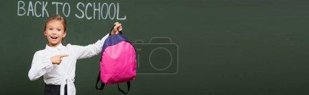 Ein lächelndes Schulmädchen zeigt auf einen rosafarbenen Rucksack in der Nähe der Schultafel