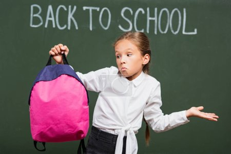 confused schoolgirl showing shrug gesture while holding backpack near chalkboard with back to school lettering