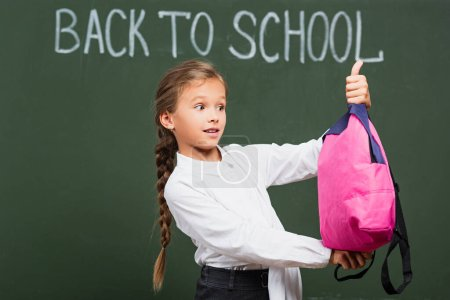 Photo for Surprised schoolgirl holding pink backpack near chalkboard with back to school lettering - Royalty Free Image