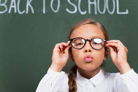 Photo pour Foyer sélectif de jolies écolières touchant les lunettes et soufflant l'air baiser près du tableau noir avec retour à l'école lettrage - image libre de droit