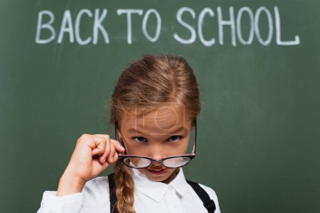 selective focus of cute schoolgirl taking off eyeglasses while looking at camera near back to school lettering on chalkboard