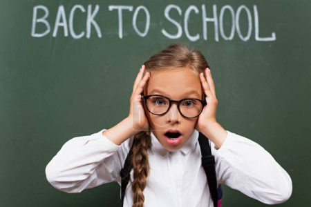 selective focus of shocked schoolgirl in eyeglasses touching head near back to school lettering on chalkboard