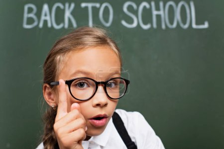 selective focus of adorable schoolgirl in eyeglasses showing idea gesture near chalkboard with back to school text