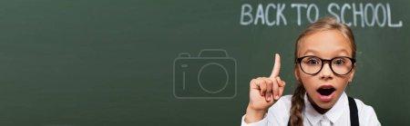 Photo pour Image horizontale d'une écolière surprise montrant un geste d'idée près d'un tableau noir avec un lettrage de retour à l'école - image libre de droit