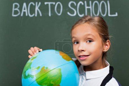enfoque selectivo de sonriente colegiala sosteniendo globo y mirando a la cámara cerca de la inscripción de la escuela en pizarra