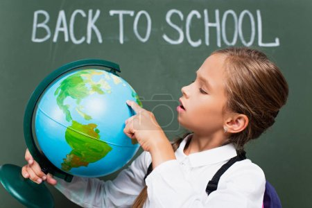 selective focus of attentive schoolgirl pointing with finger at globe near back to school lettering on chalkboard