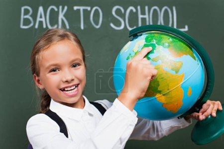 enfoque selectivo de colegiala feliz señalando con el dedo en el globo cerca de la inscripción de la escuela en pizarra