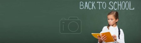 horizontal image of surprised schoolgirl looking at copy book near chalkboard with back to school lettering