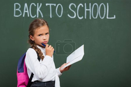Photo for Upset schoolgirl with backpack holding notebook and pen near chalkboard with back to school lettering - Royalty Free Image