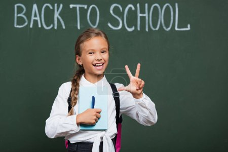 Photo for Happy schoolgirl with book and pen showing victory gesture near chalkboard with back to school text - Royalty Free Image