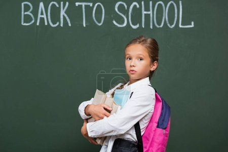 Photo for Discouraged schoolgirl with backpack holding books near chalkboard with back to school inscription - Royalty Free Image