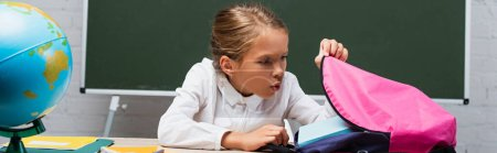 panoramic shot of surprised schoolgirl looking into backpack while sitting at desk near globe and chalkboard