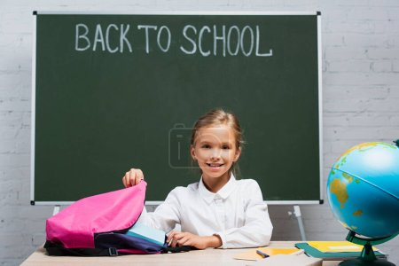 Photo for Smiling schoolgirl taking books from backpack while sitting at desk near chalkboard with back to school lettering - Royalty Free Image