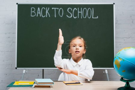 Photo for Adorable schoolgirl raising hand while sitting at desk near globe and chalkboard with back to school inscription - Royalty Free Image