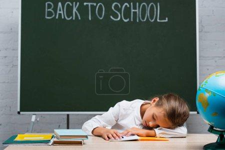 colegiala agotada durmiendo en el escritorio cerca de globo y pizarra con letras de vuelta a la escuela