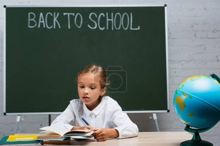 attentive schoolgirl reading book while sitting at desk near globe and chalkboard with back to school inscription