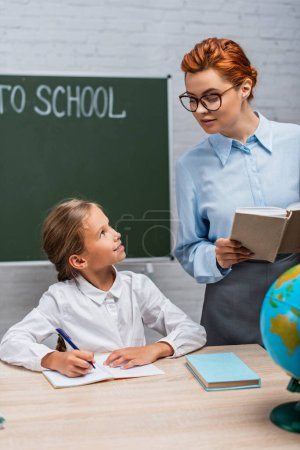 Photo for Smiling teacher looking at schoolgirl sitting at desk and writing in notebook - Royalty Free Image