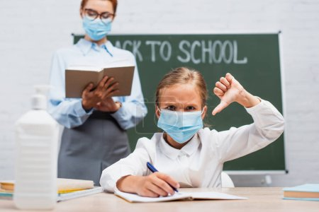 Photo for Selective focus of displeased schoolgirl in protective mask showing thumb down, and teacher standing near chalkboard with book - Royalty Free Image