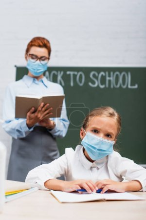 Photo for Selective focus of bored schoolgirl in protective mask looking at camera, and teacher standing near chalkboard with back to school lettering - Royalty Free Image