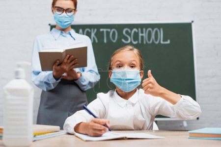 Photo for Selective focus of schoolgirl in protective mask showing thumb up, and teacher standing near chalkboard with back to school lettering - Royalty Free Image