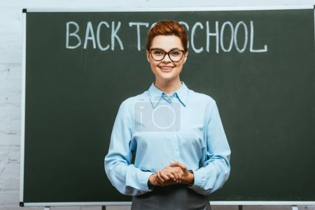 cheerful teacher standing with clenched hands near chalkboard with back to school inscription