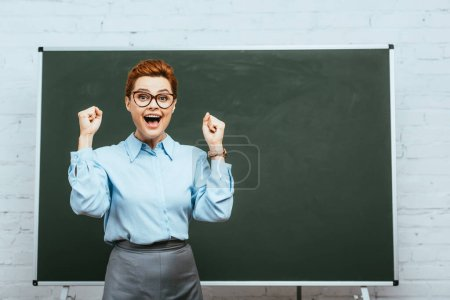 excited teacher showing winner gesture and looking at camera while standing near chalkboard