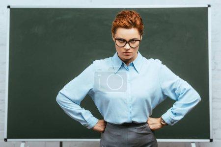 Photo pour Professeur strict dans les lunettes en regardant la caméra tout en se tenant avec les mains sur les hanches près du tableau - image libre de droit