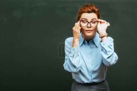 Photo pour Jeune professeur touchant les lunettes et les yeux tout en se tenant près du tableau - image libre de droit