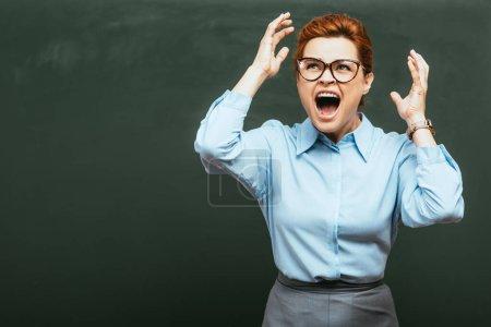Photo pour Professeur irrité gesticulant et criant près du tableau - image libre de droit